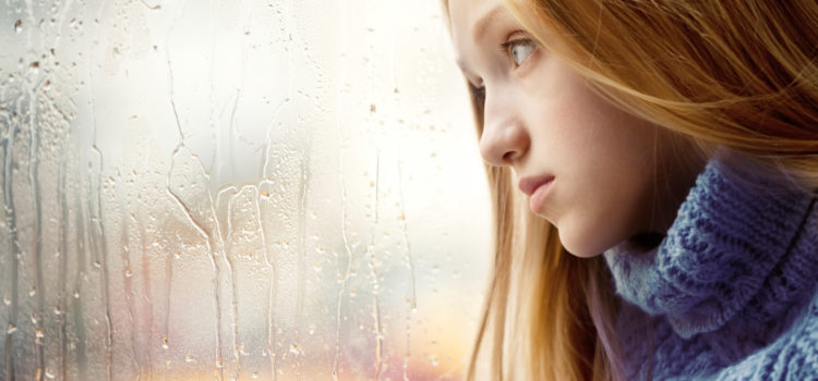 Emotional Portrait of a sad Girl with long blonde Hair. She is looking through a Window in the Rainy Autumn Day